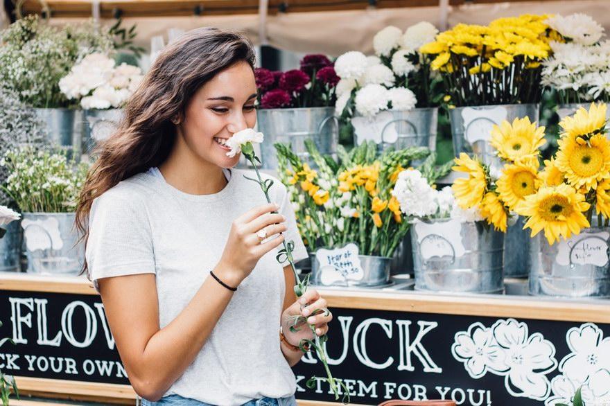 Kobieta trzymająca kwiatek. Uśmiechnięta. Oferta konta za zero w banku PKO BP.
