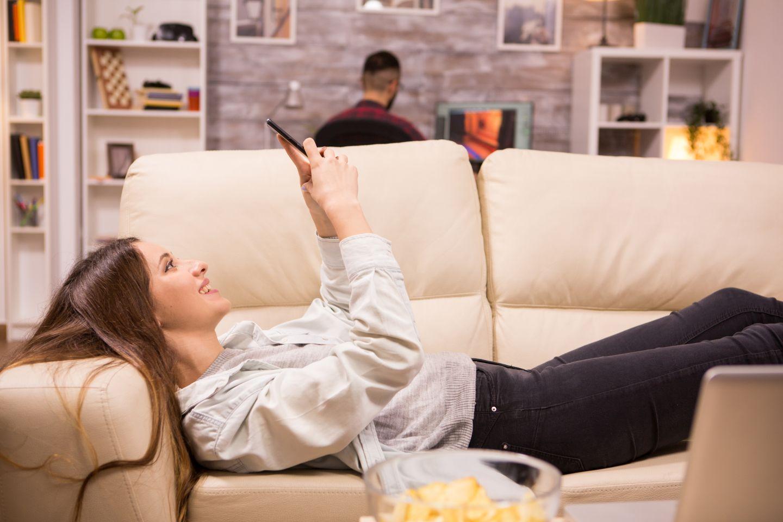 Piękna kobieta leżąca na kanapie i przeglądająca oferty kredytów.